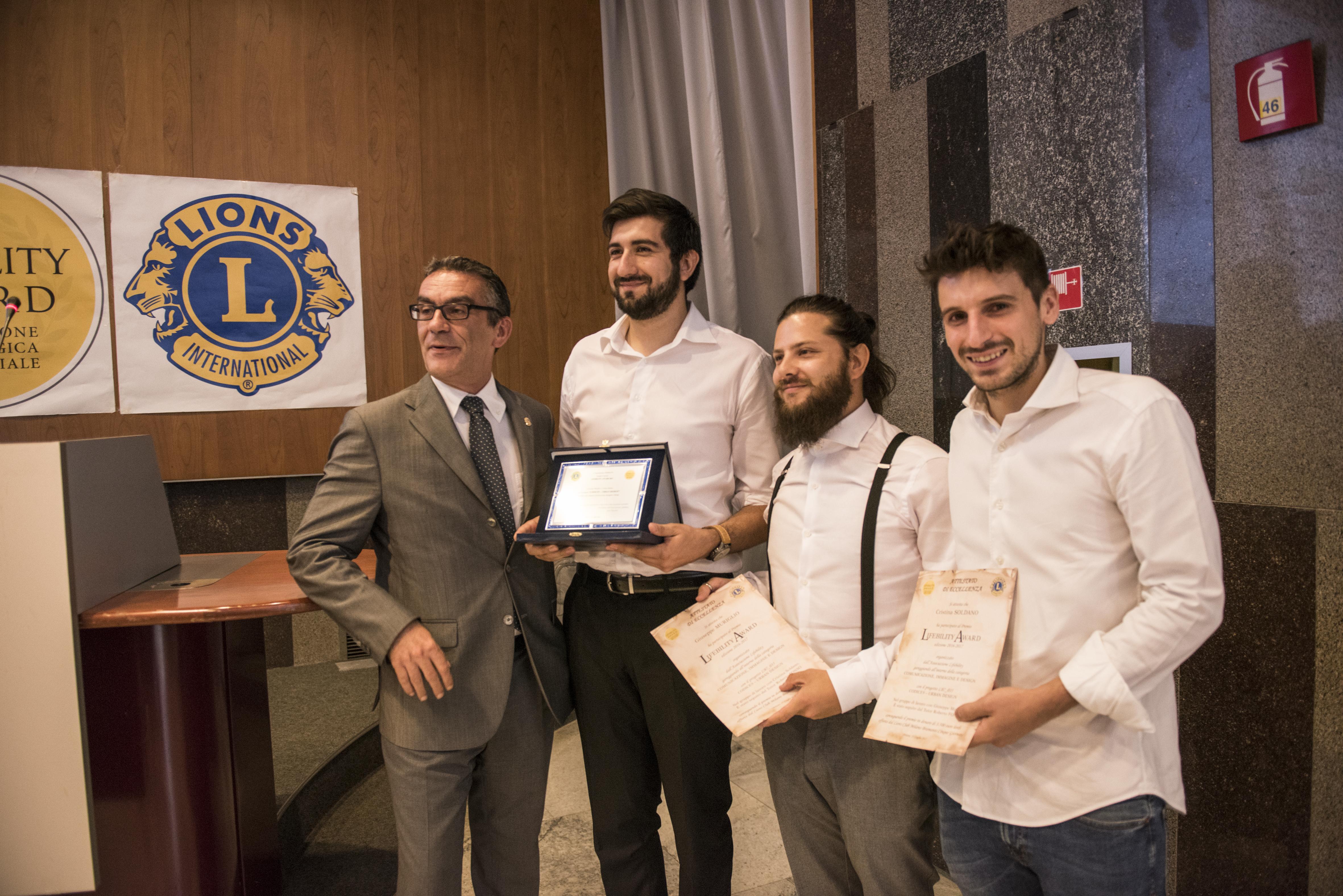 """Marco Stracquadaini (Lions Club Milano Bramante Cinque Giornate) premia il progetto """"Codice9 – Urban Design""""."""